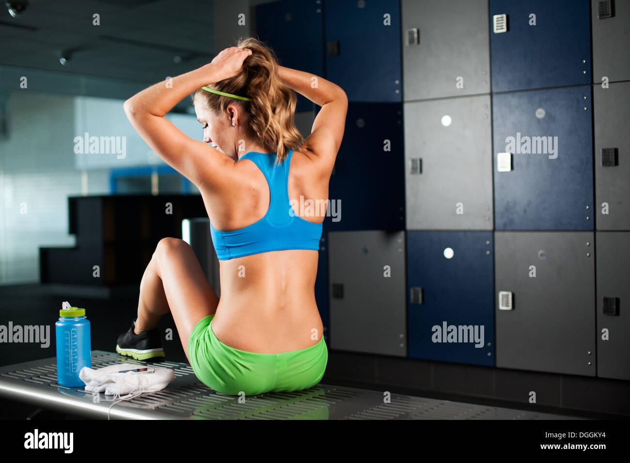 Junge Frau Pferdeschwanz binden, im Fitness-Studio Stockbild