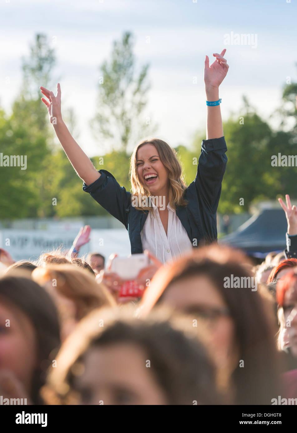 Eine Frau in einer Menschenmenge auf einem Konzert. Stockbild