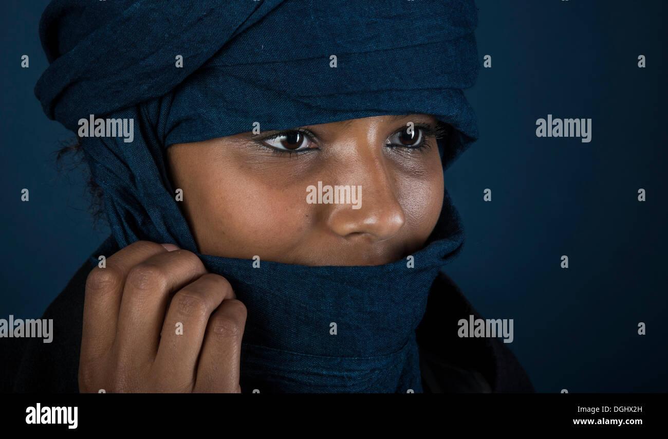 Tuareg Mädchen, Targia, mit einem Chech verschleiert, Porträt, Gesicht eingehüllt auf mysteriöse Weise mit der Hand, Algerien, Nordafrika, Afrika Stockbild