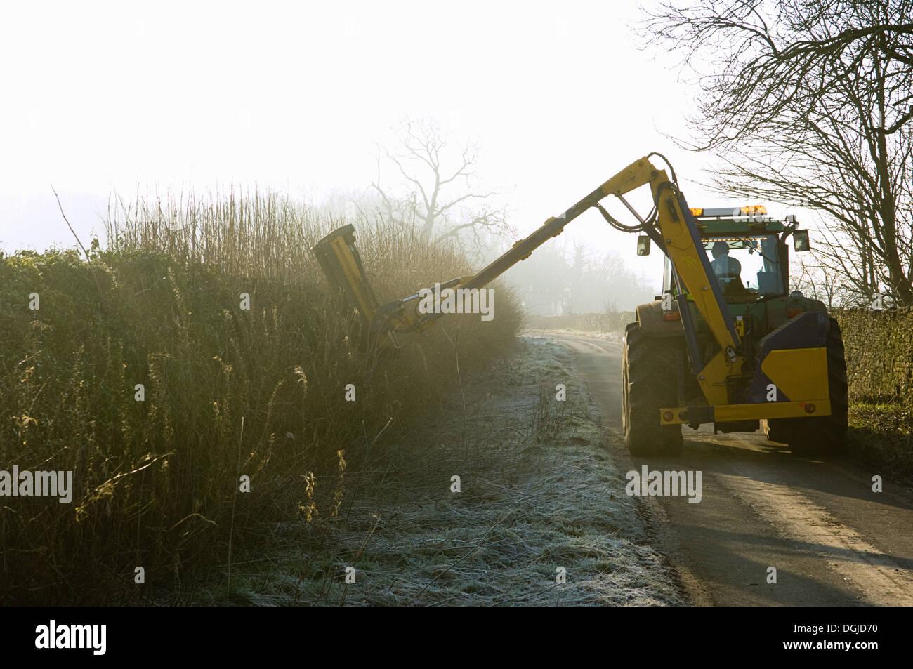 Traktor schneiden Hecke entlang Landstraße Stockbild