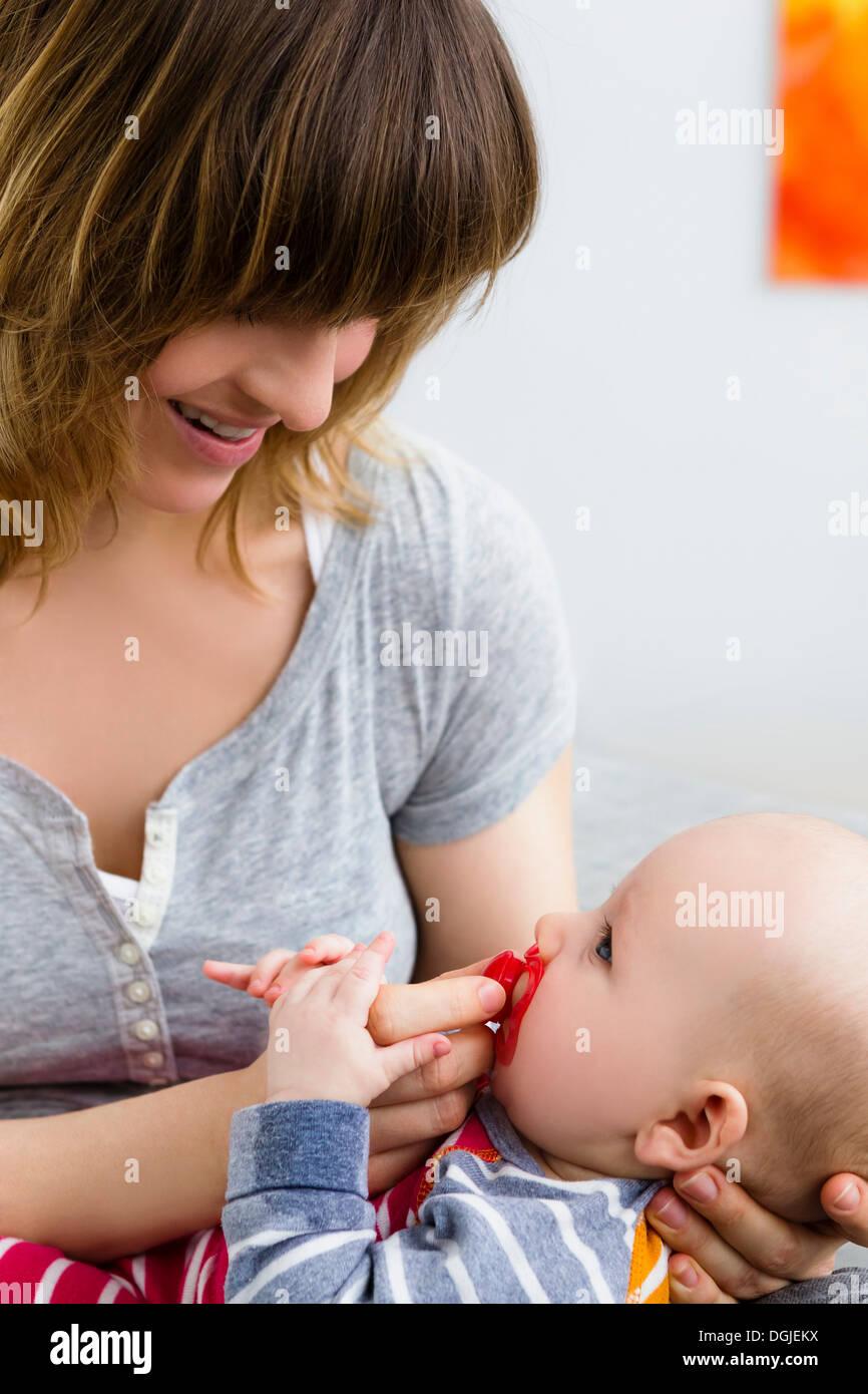 Sohn von Mutter und Baby mit Schnuller im Mund Stockbild
