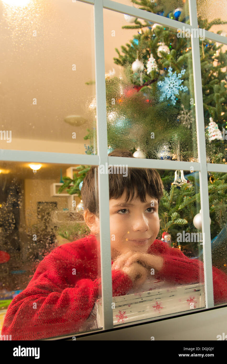 Junge starrte aus dem Fenster am Heiligabend Stockbild