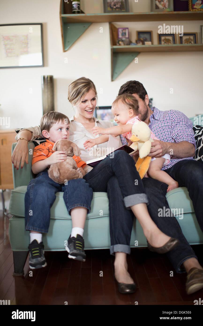 Eltern mit zwei Kindern auf sofa Stockbild