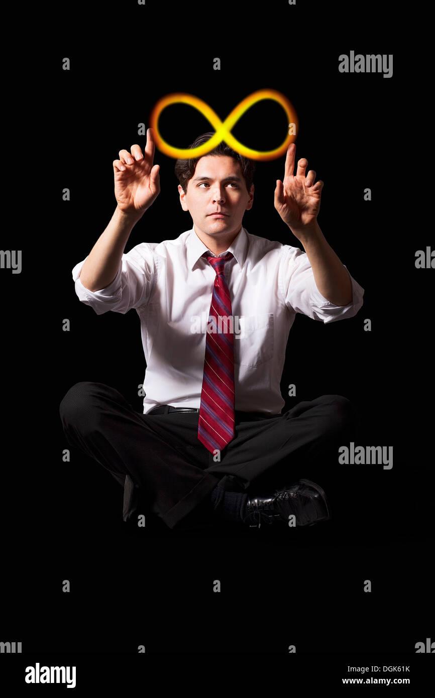Geschäftsmann, beleuchtete Unendlichkeitssymbol berühren Stockbild