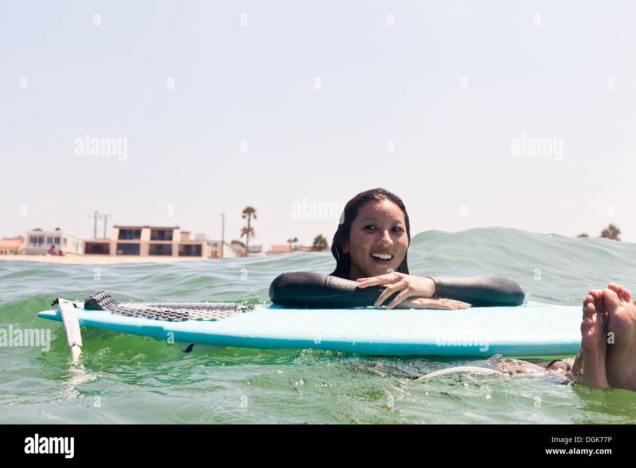Frau schwebt mit Surfbrett, Hermosa Beach, Kalifornien, USA Stockbild