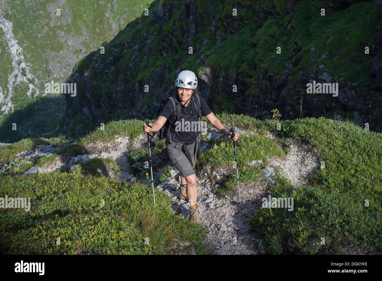 Kletterausrüstung Rucksack : Frau mit einem rucksack felsen klettern helm und wanderstöcke