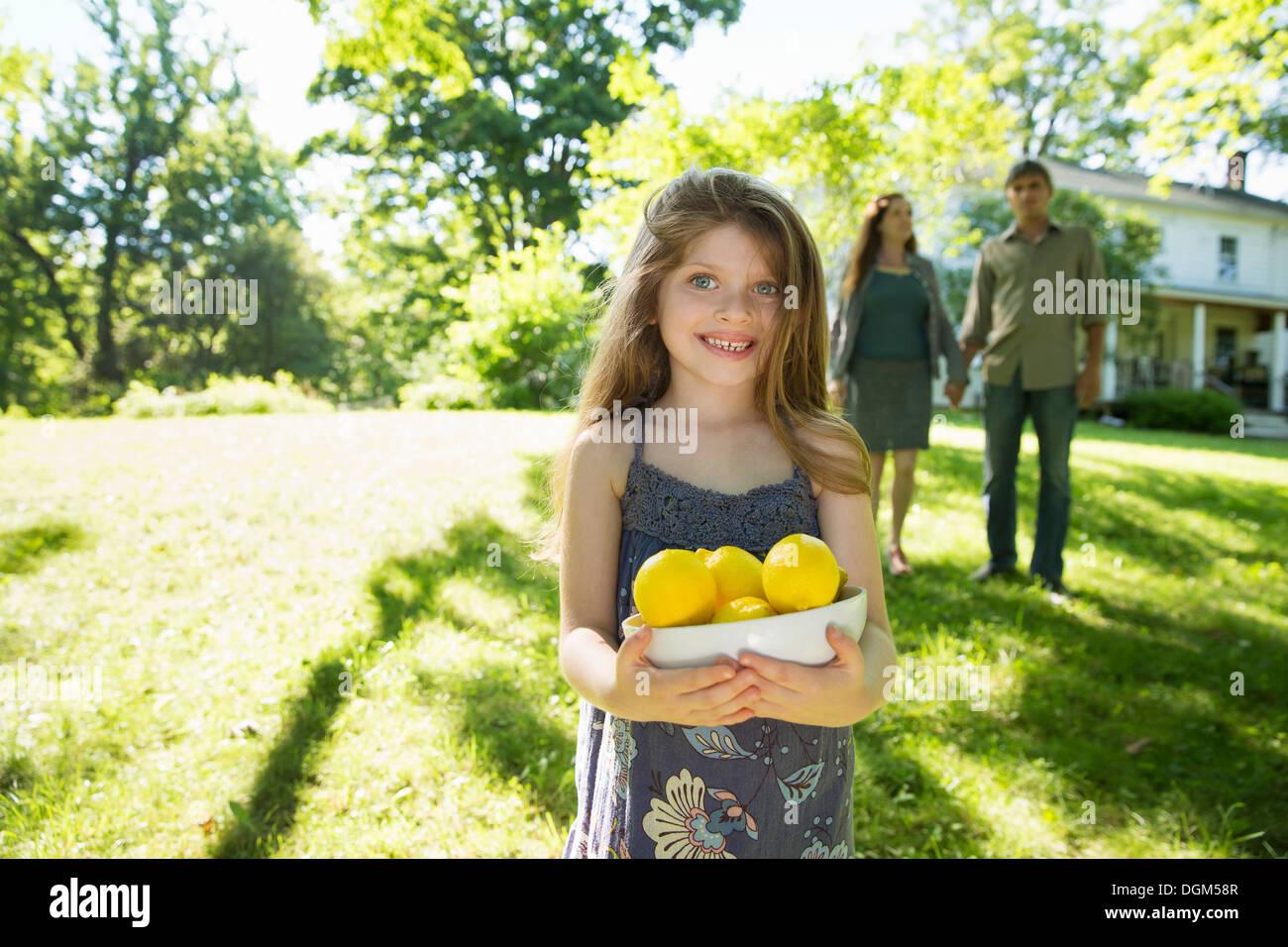 Bauernhof. Kinder und Erwachsene gemeinsam. Ein Mädchen mit einer Kiste von Zitronen, frisches Obst. Zwei Erwachsene im Hintergrund. Stockbild