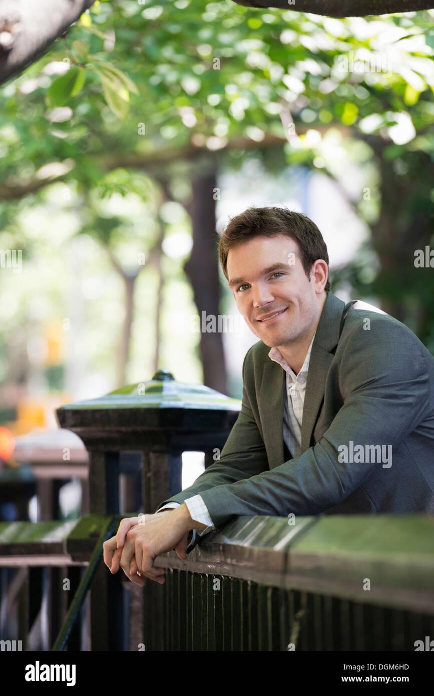 Sommer. Ein junger Mann in einem grauen Anzug. Stockbild