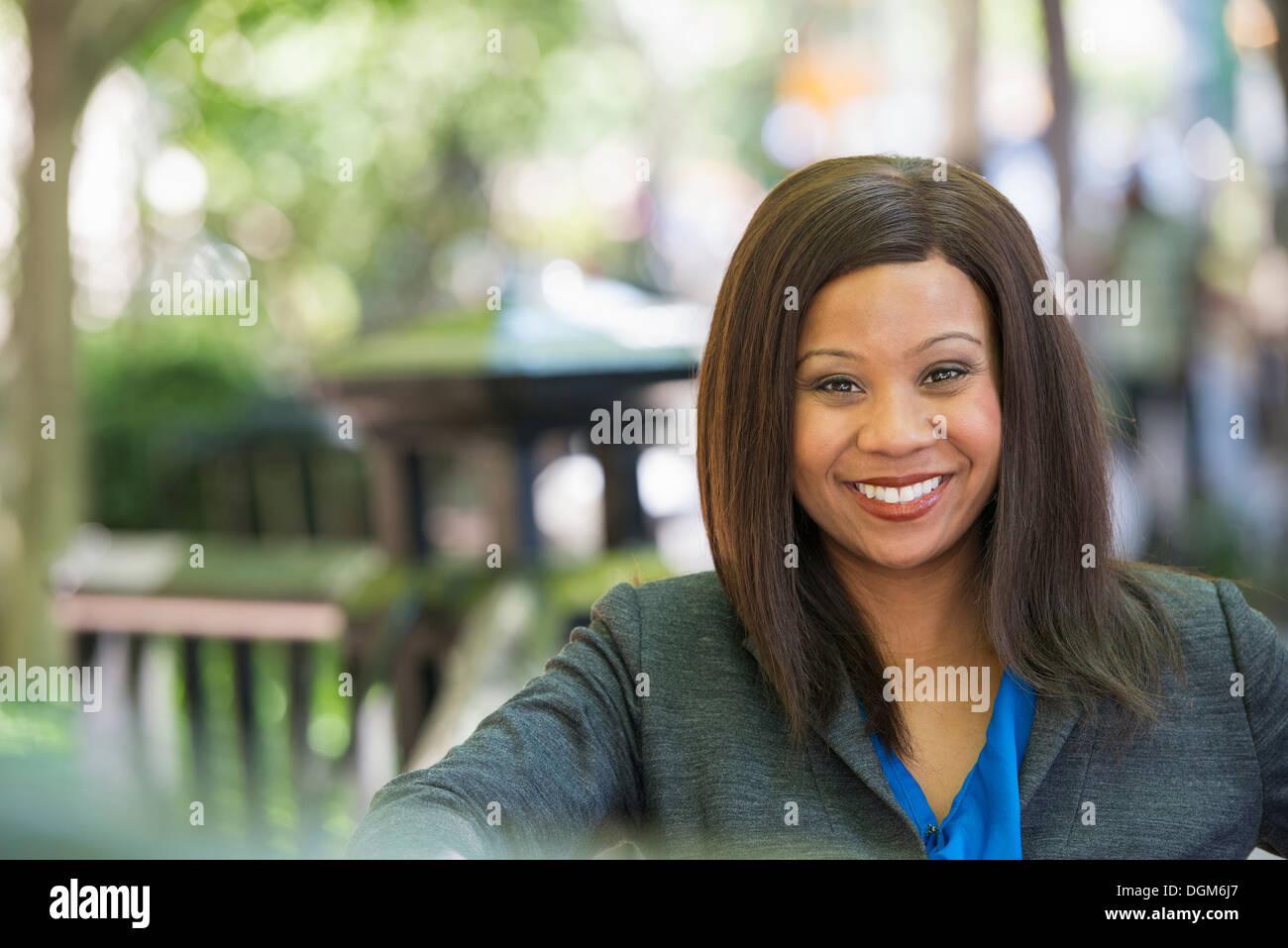 Sommer. Eine Frau in einem grauen Anzug mit einem leuchtend blauen Shirt. Stockbild