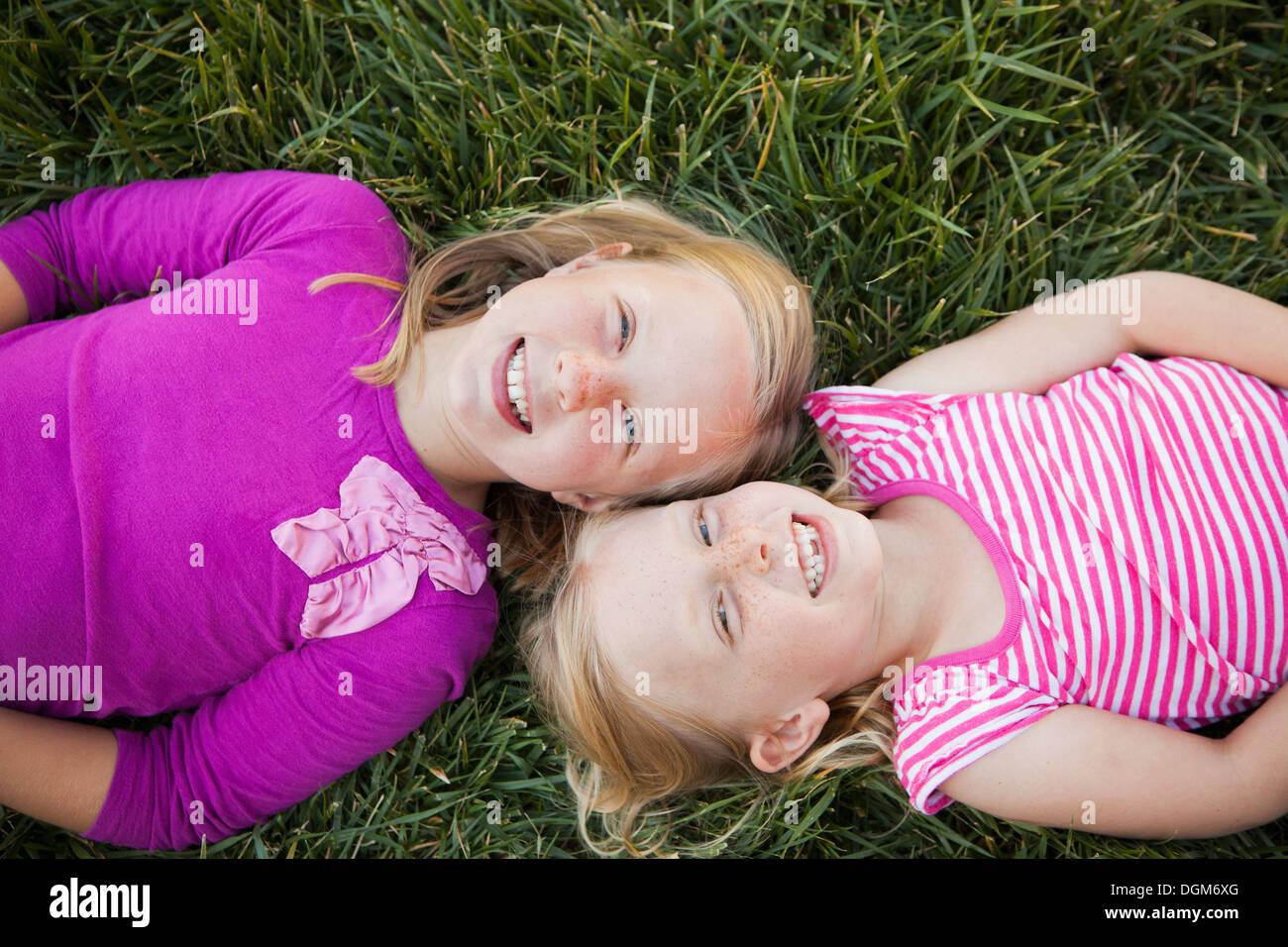 Ein Porträt von zwei Schwestern, die lächelnd. Ansicht von oben, von zwei Mädchen liegen auf dem Rücken im Gras, die Köpfe zusammen. Stockbild