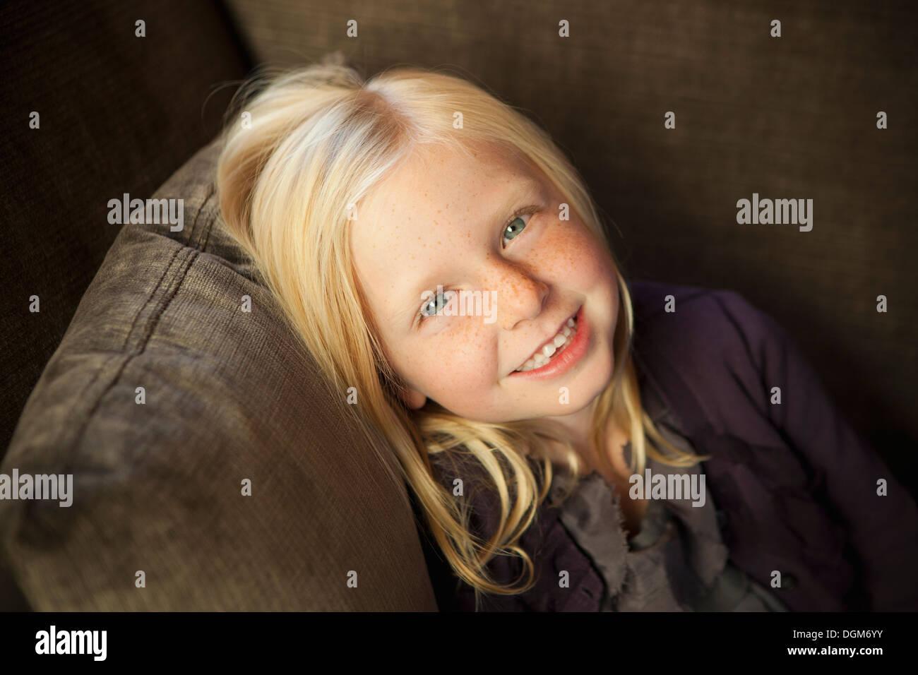 Ein Mädchen sitzt auf einer Couch, lächelnd in die Kamera. Stockfoto