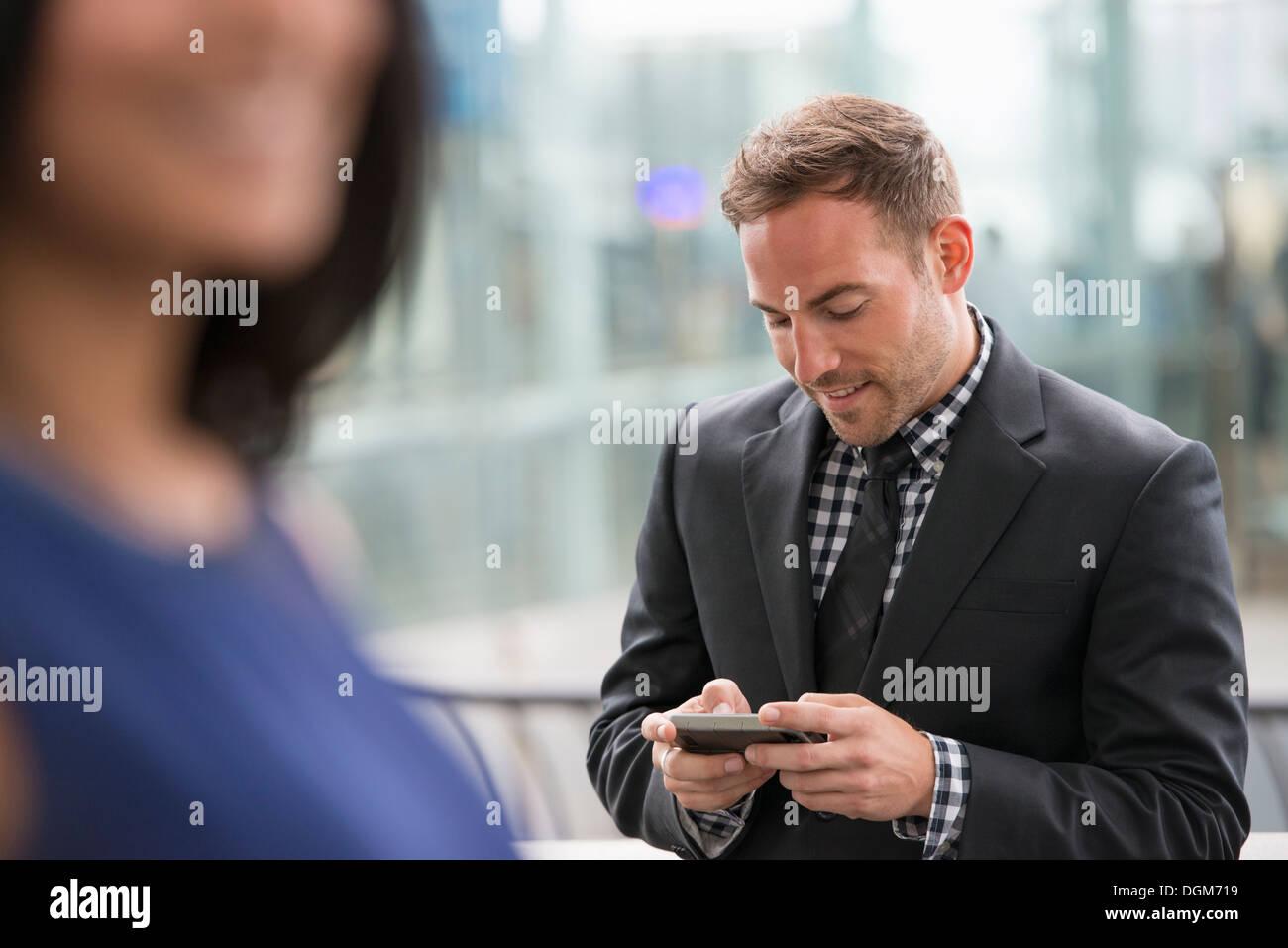 Ein Mann in einem Anzug überprüft sein Telefon. Eine Frau im Vordergrund. Stockbild