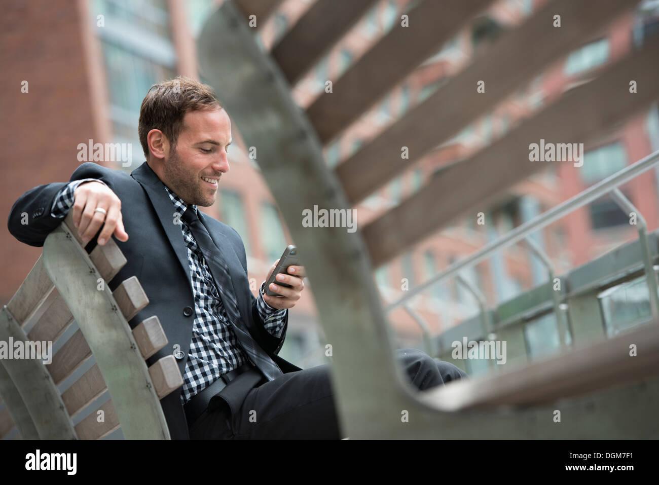 Business-Leute. Ein Mann in einem Anzug, auf einer Bank sitzen. Stockbild