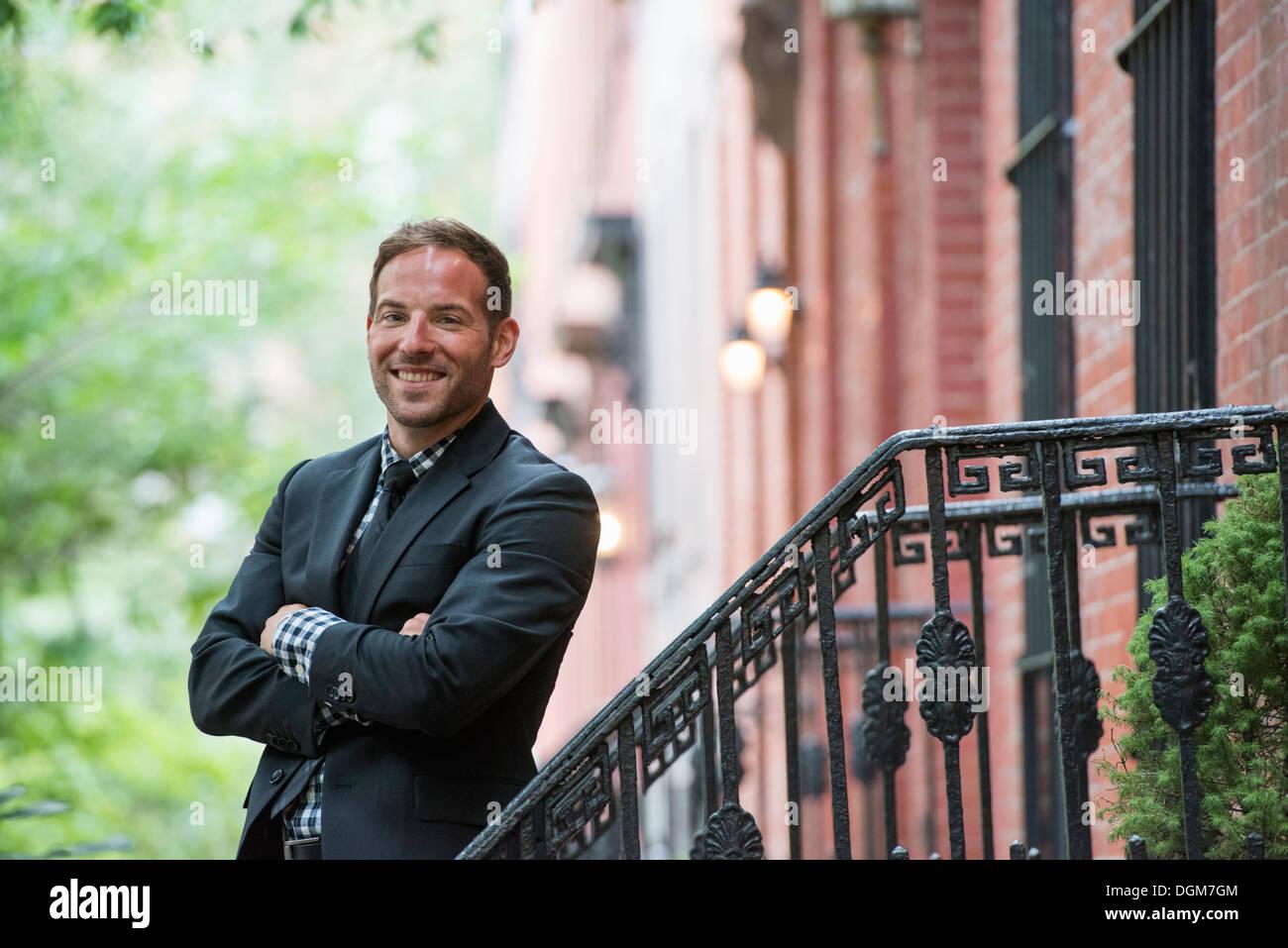Business-Leute. Ein Mann in einem Anzug auf den Stufen eines Brownstone-Gebäudes. Arme verschränkt. Stockbild