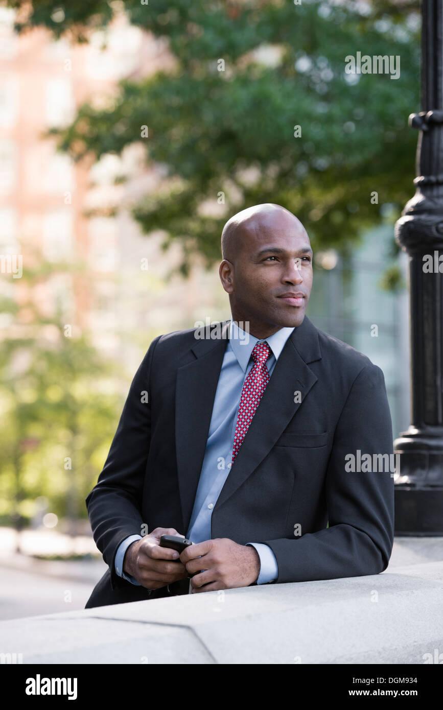 Business-Leute. Ein Mann in einem Anzug, stützte sich auf eine Balustrade unter einem Laternenmast. Warten. Stockbild