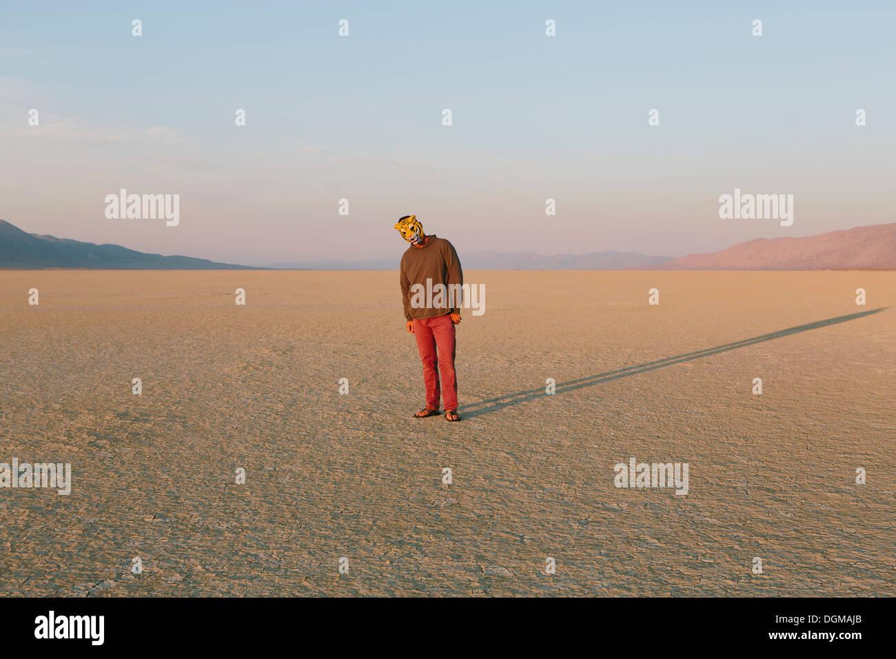 Die Landschaft der Black Rock Desert in Nevada. Ein Mann trägt eine Tiermaske. Wirft einen langen Schatten auf dem Boden. Stockbild