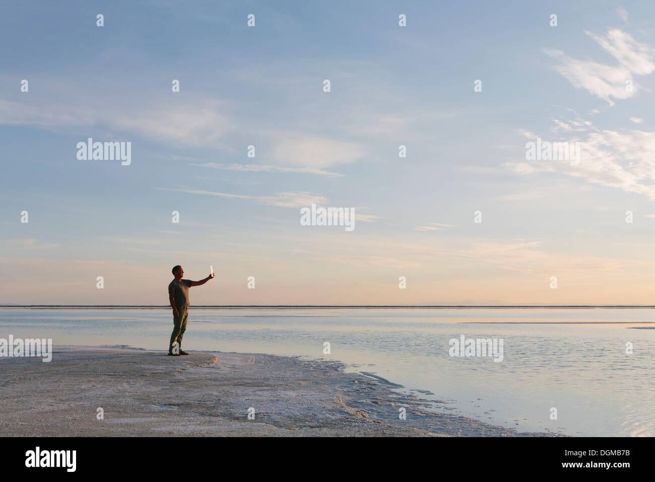 Ein Mann steht am Rand des überfluteten Bonneville Salt Flats in der Abenddämmerung, Fotografieren mit einem Tablet-Gerät. Stockbild