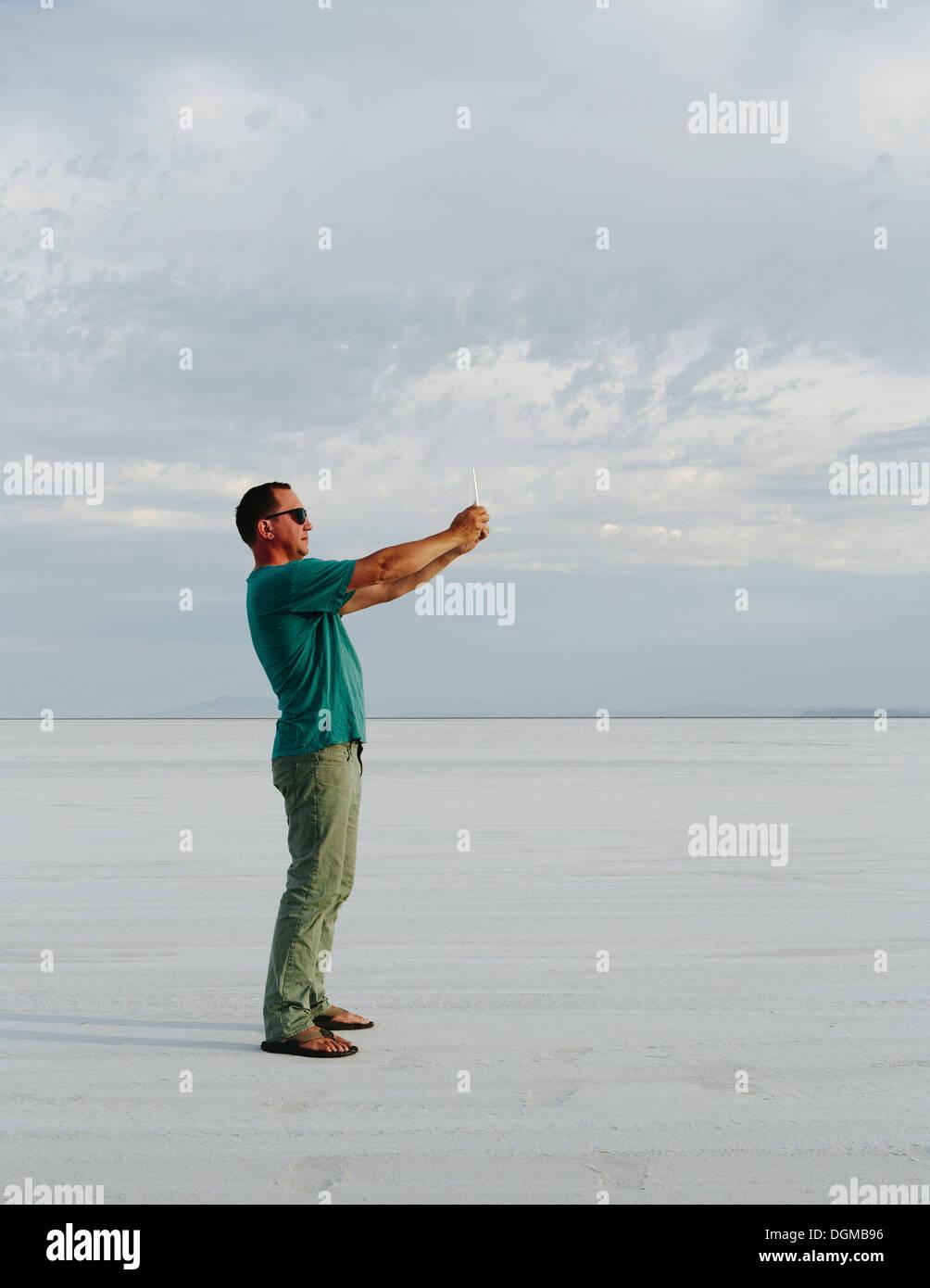 Ein Mann steht auf den Bonneville Salt Flats, Fotografieren mit Tablet-Gerät, in der Dämmerung. Stockbild