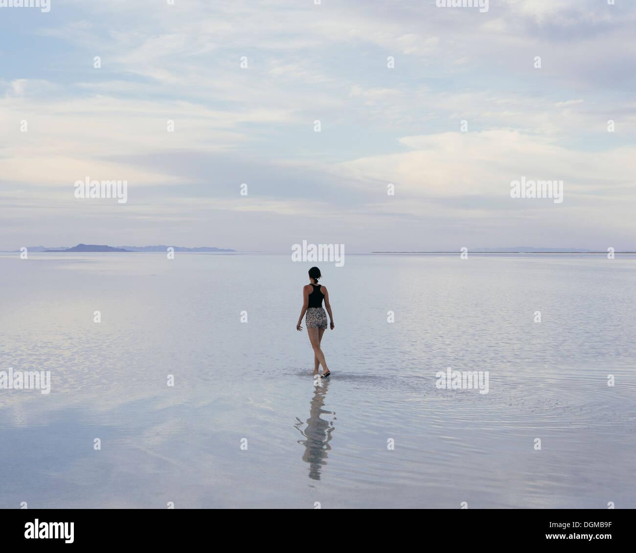 Eine Frau stand auf den überfluteten Bonneville Salt Flats in der Abenddämmerung. Reflexionen im seichten Wasser. Stockbild