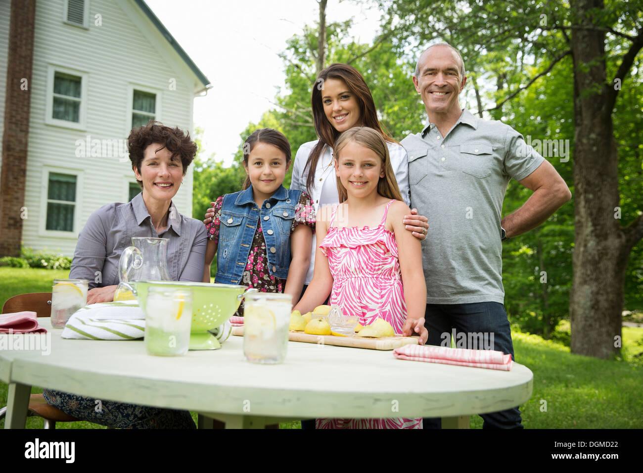 Ein Sommer-Familientreffen auf einem Bauernhof. Fünf Menschen posieren neben dem Tisch, wo ein Kind frische Limonade macht. Stockbild