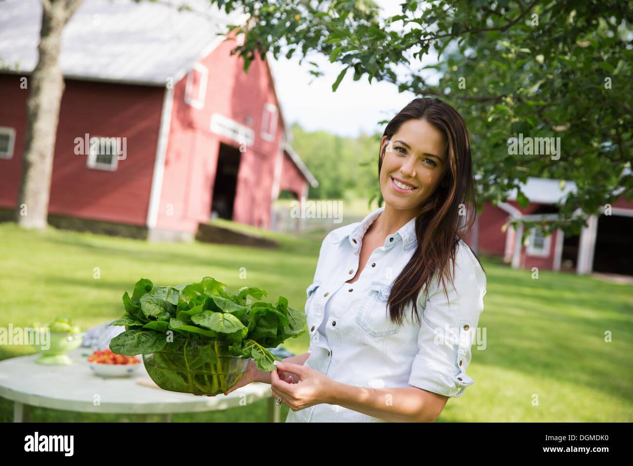 Ein Sommer Familientreffen Bauernhof junge Frau lange braune Haare rollte Ärmel tragen große Schüssel mit frischem grünen Salat Blätter Stockbild