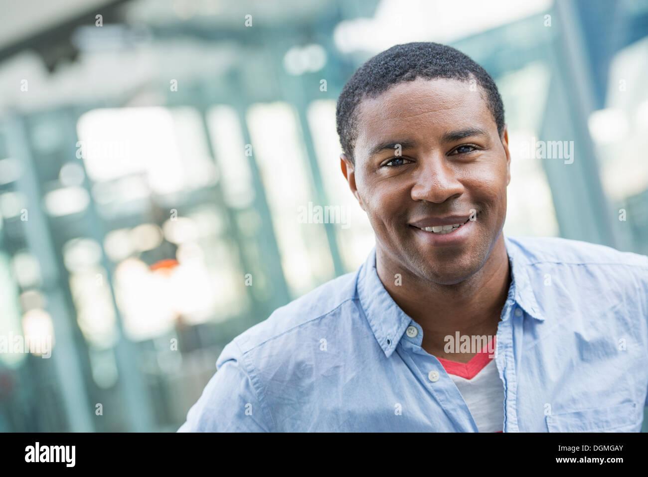 Sommer in der Stadt. Geschäftsleute in Freizeitkleidung. Ein hübscher Mann in ein blaues Hemd. Stockbild