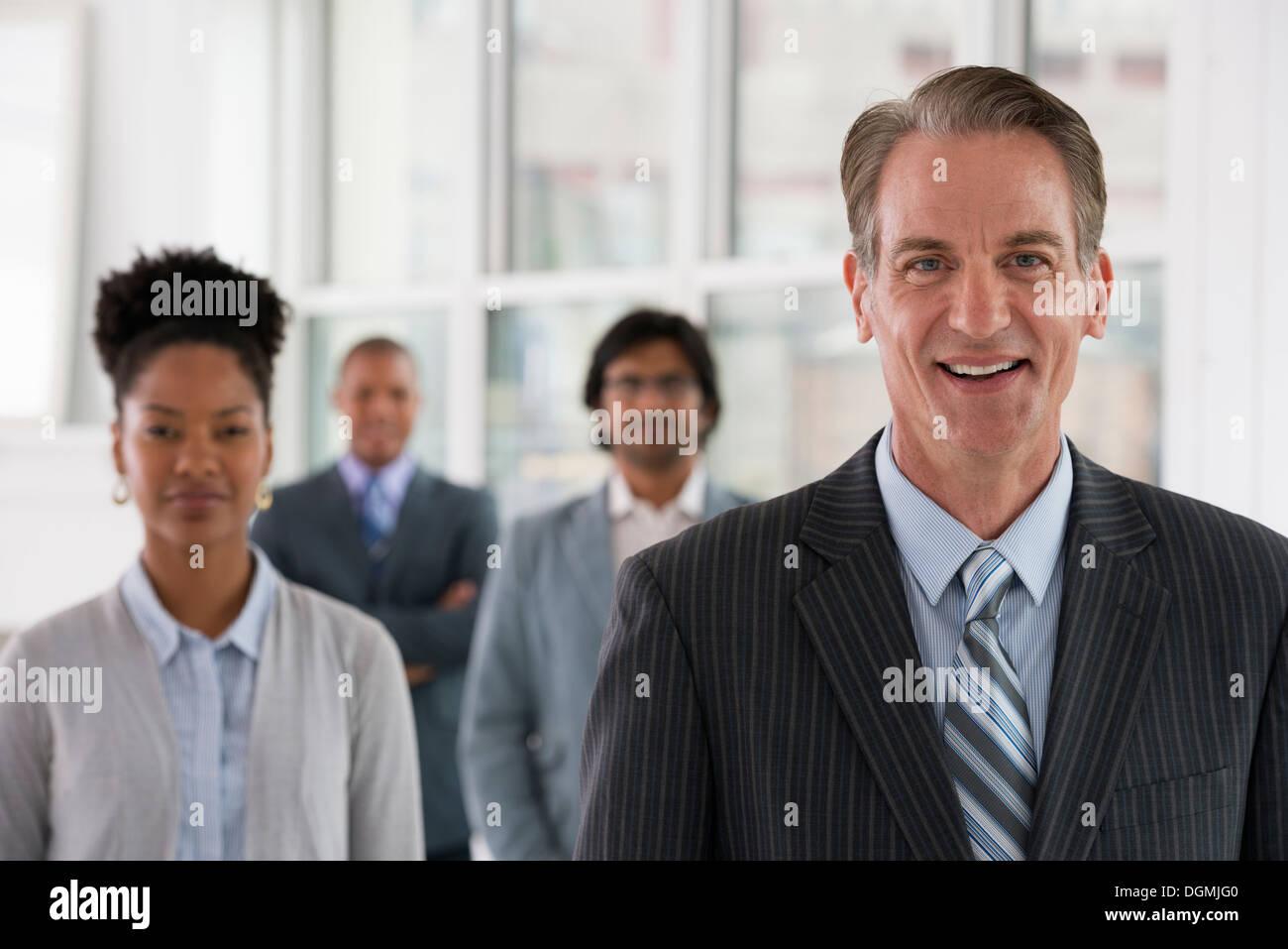Business-Leute. Vier Personen, drei Männer und eine Frau. Stockbild