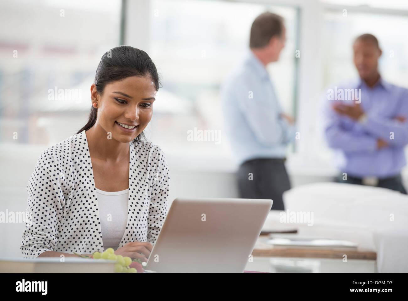 Büroalltag. Eine Frau sitzt an einem Schreibtisch mit einem Laptopcomputer. Zwei Männer im Hintergrund. Stockbild