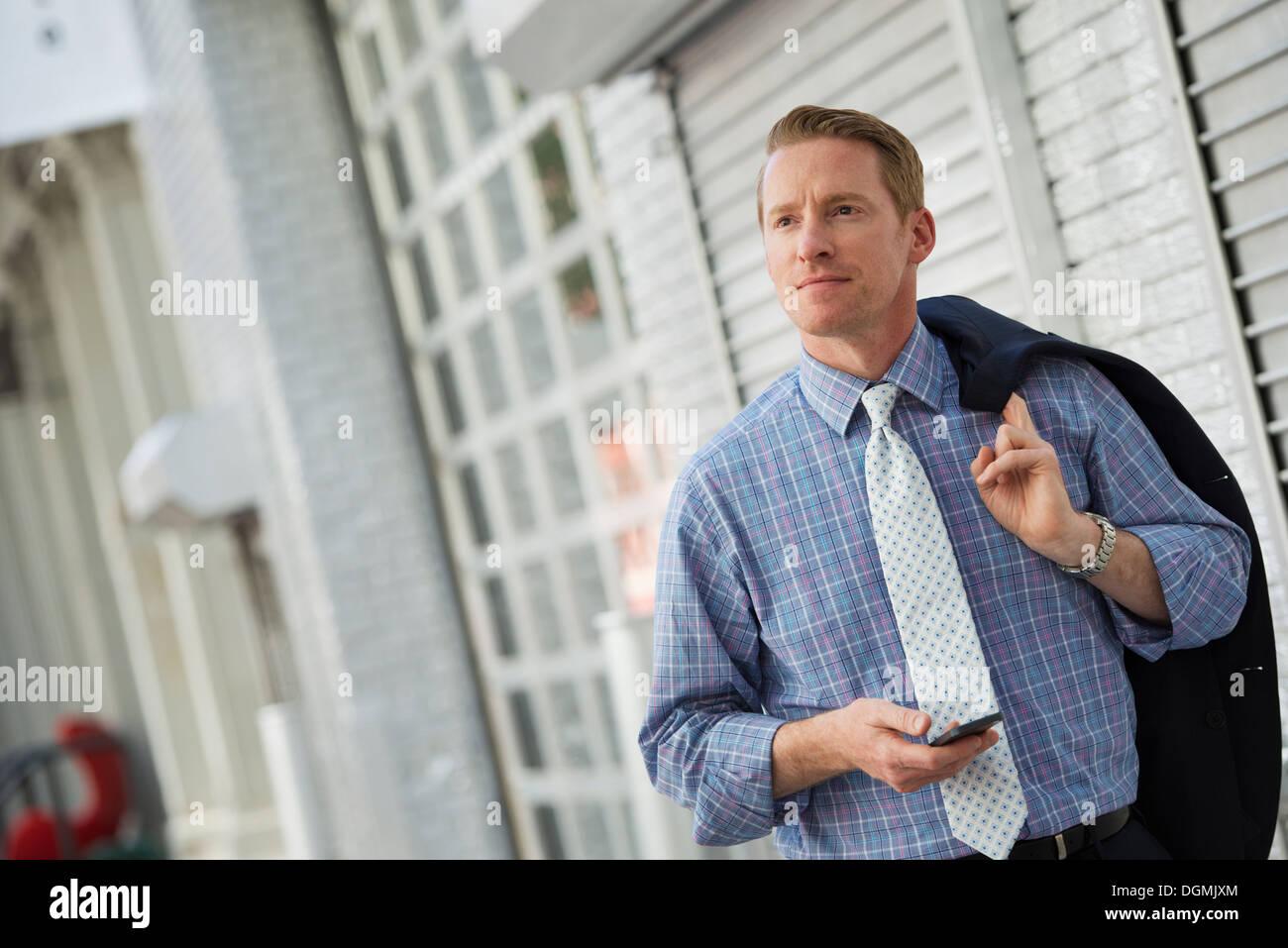 Ein Mann mit seiner Jacke, die über die Schulter geschlungen überprüft sein Telefon. Stockbild