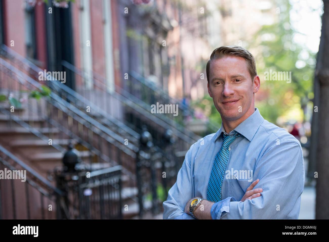 Ein Mann in ein blaues Hemd und blaue Krawatte mit Armen gefaltet, auf dem Bürgersteig stehen Stockbild