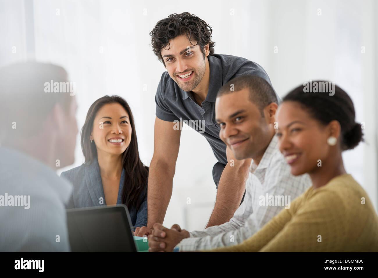 Eine Multi ethnische Gruppe von Menschen rund um einen Tisch, Männer und Frauen. Teamarbeit. Treffen. Stockbild