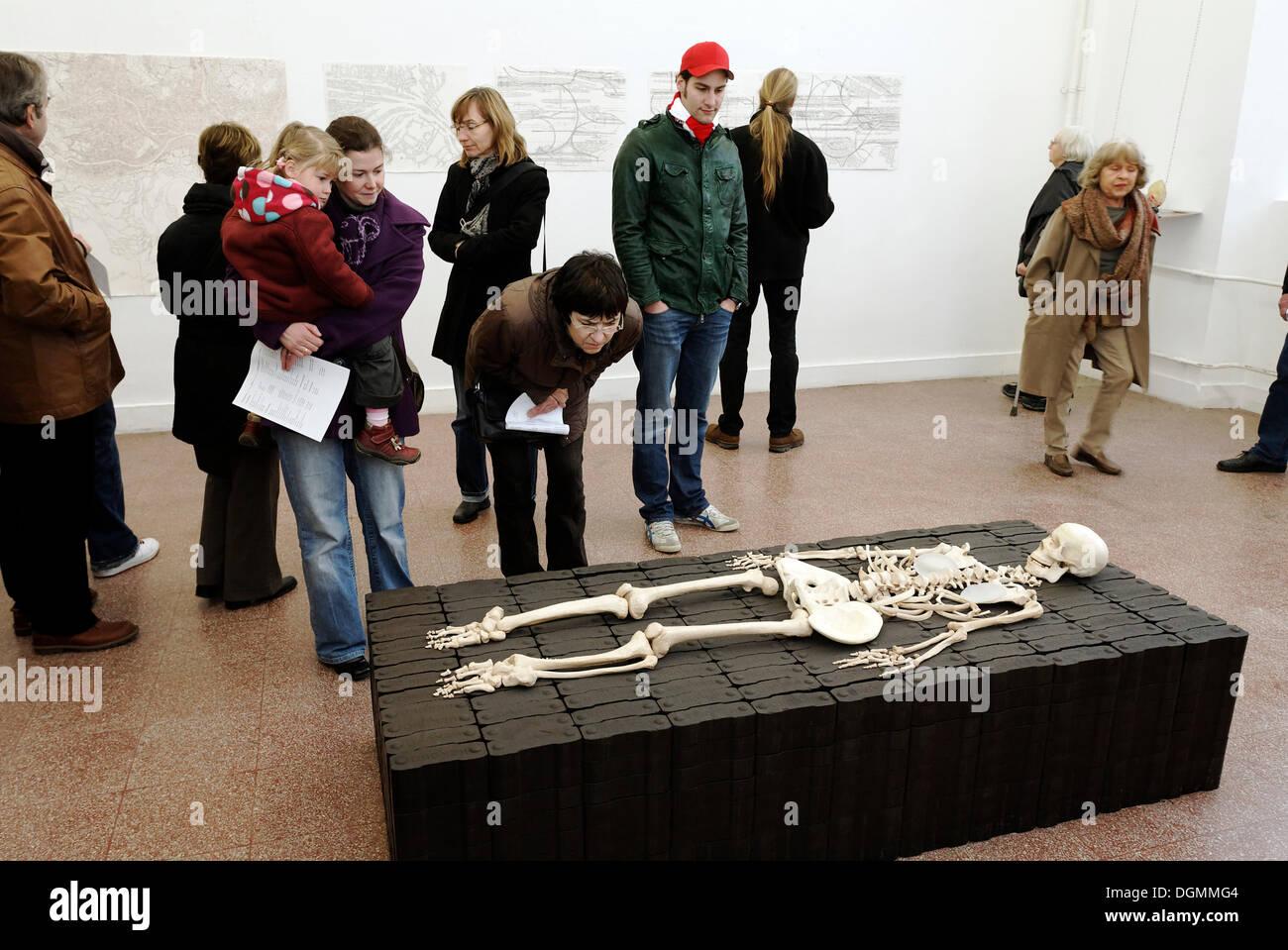Besucher schauen Sie sich eine Skulptur, menschliches Skelett auf Briketts, liegend Tour Kunstakademie Kunstakademie in Düsseldorf Stockbild