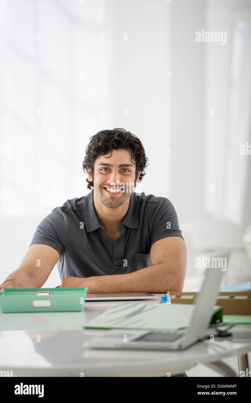 Geschäft. Ein Mann sitzt in einer entspannter Pose hinter einem Schreibtisch. Stockbild