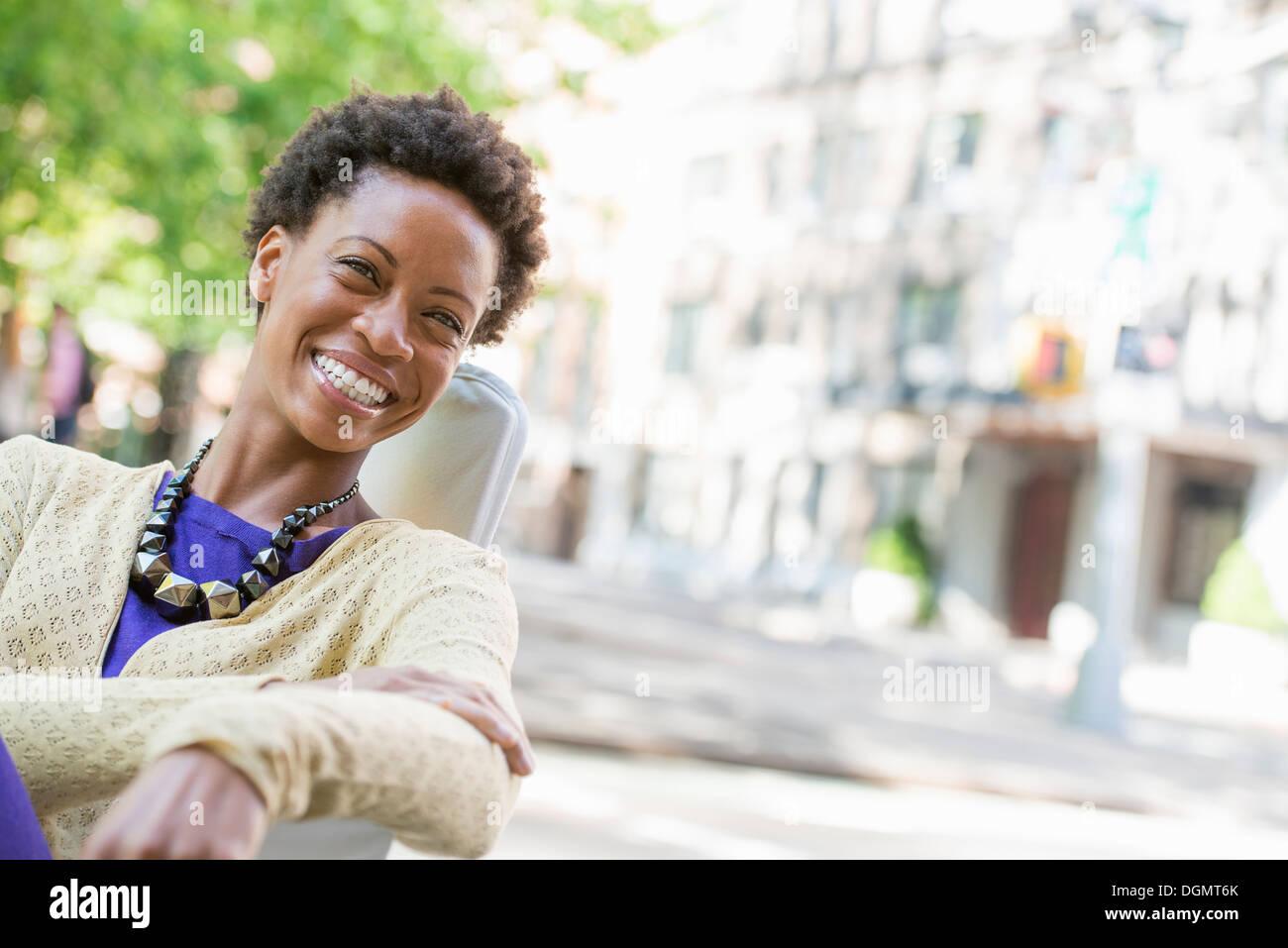 Leben in der Stadt. Eine Frau sitzt an der frischen Luft in einem Stadtpark. Stockbild