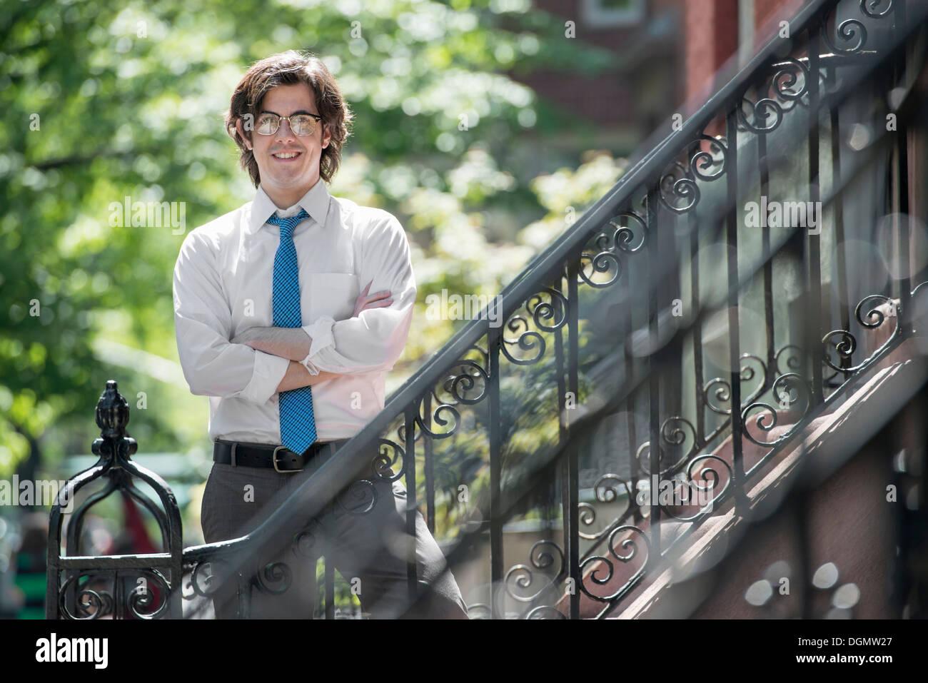 Stadt. Ein junger Mann in w weißes Hemd und eine blaue Krawatte, stehend mit Armen gefaltet außerhalb eines Stadthauses, auf den Stufen. Stockbild