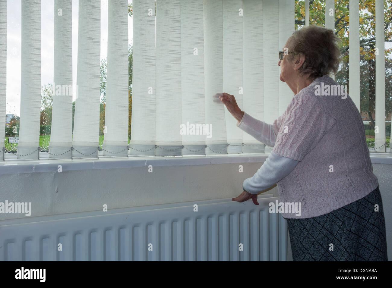 Neunzig Jahre alte Dame Blick aus Fenster von ihrem eigenen Haus mit Hand am Heizkörper Stockbild