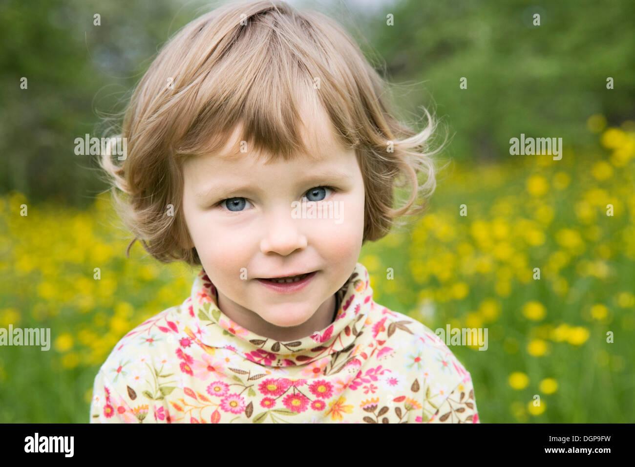 kleine mädchen stehen auf einer blumenwiese, porträt