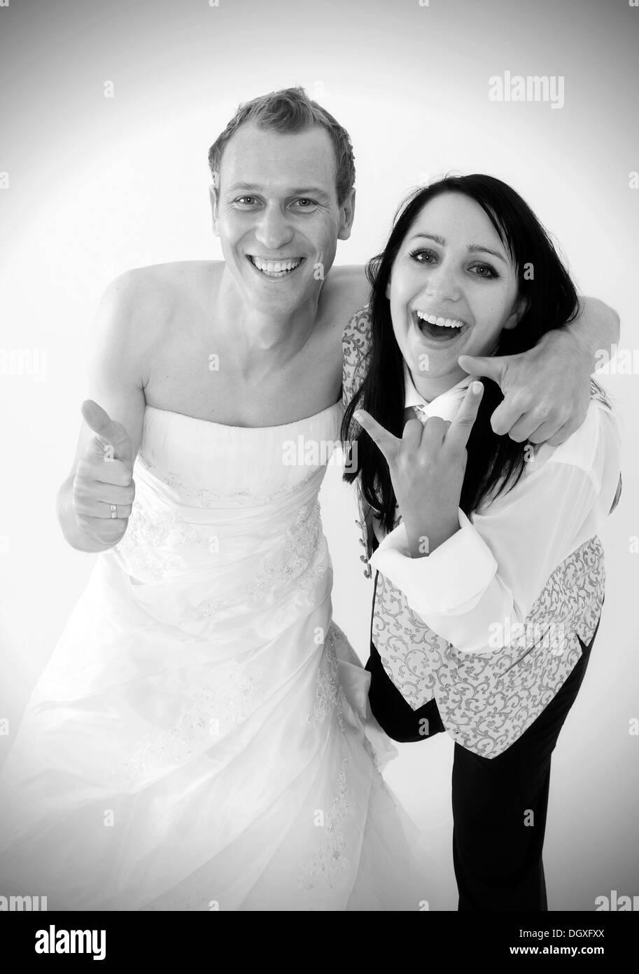 Lächelnde Braut trägt einen Anzug und ein Bräutigam trägt ein ...