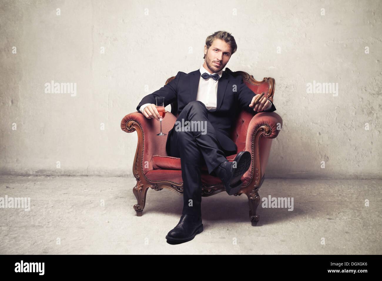Mann sitzt auf einem Vintage Sessel Stockbild
