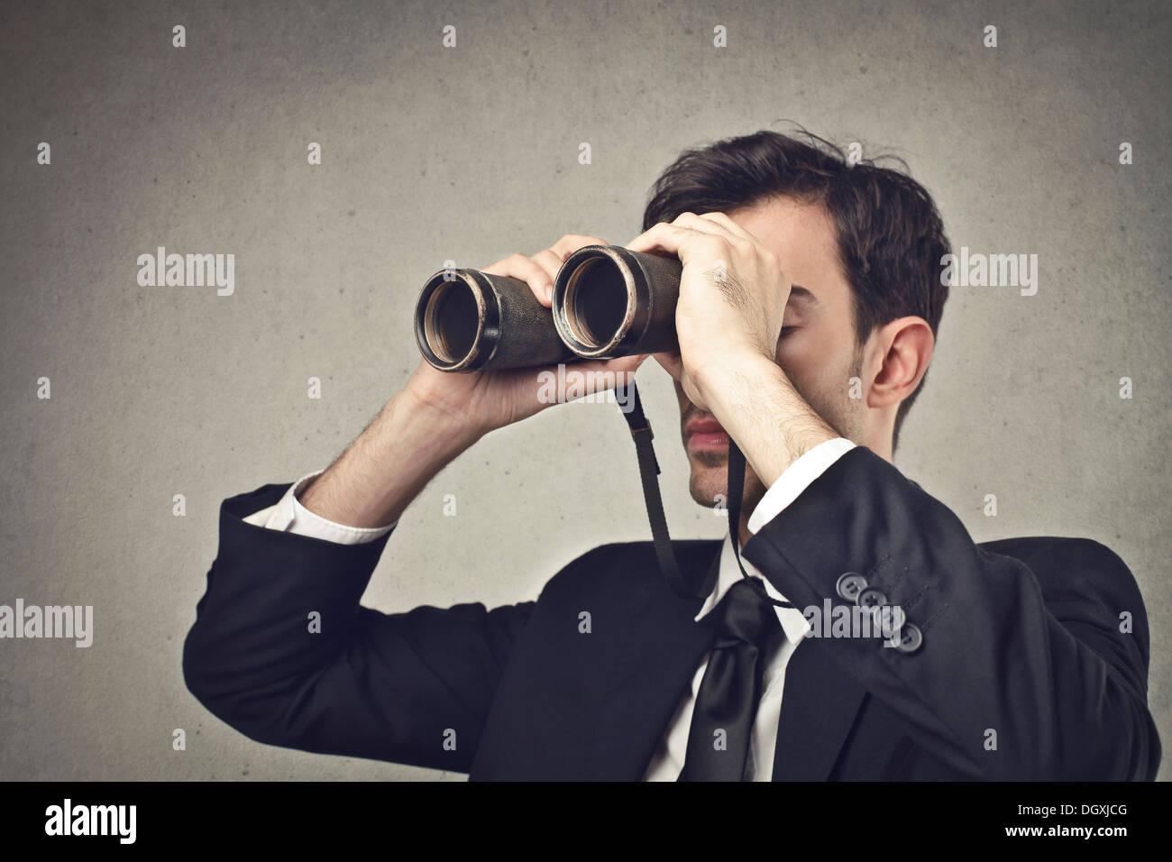 Junger Geschäftsmann mit Fernglas beobachten Stockbild