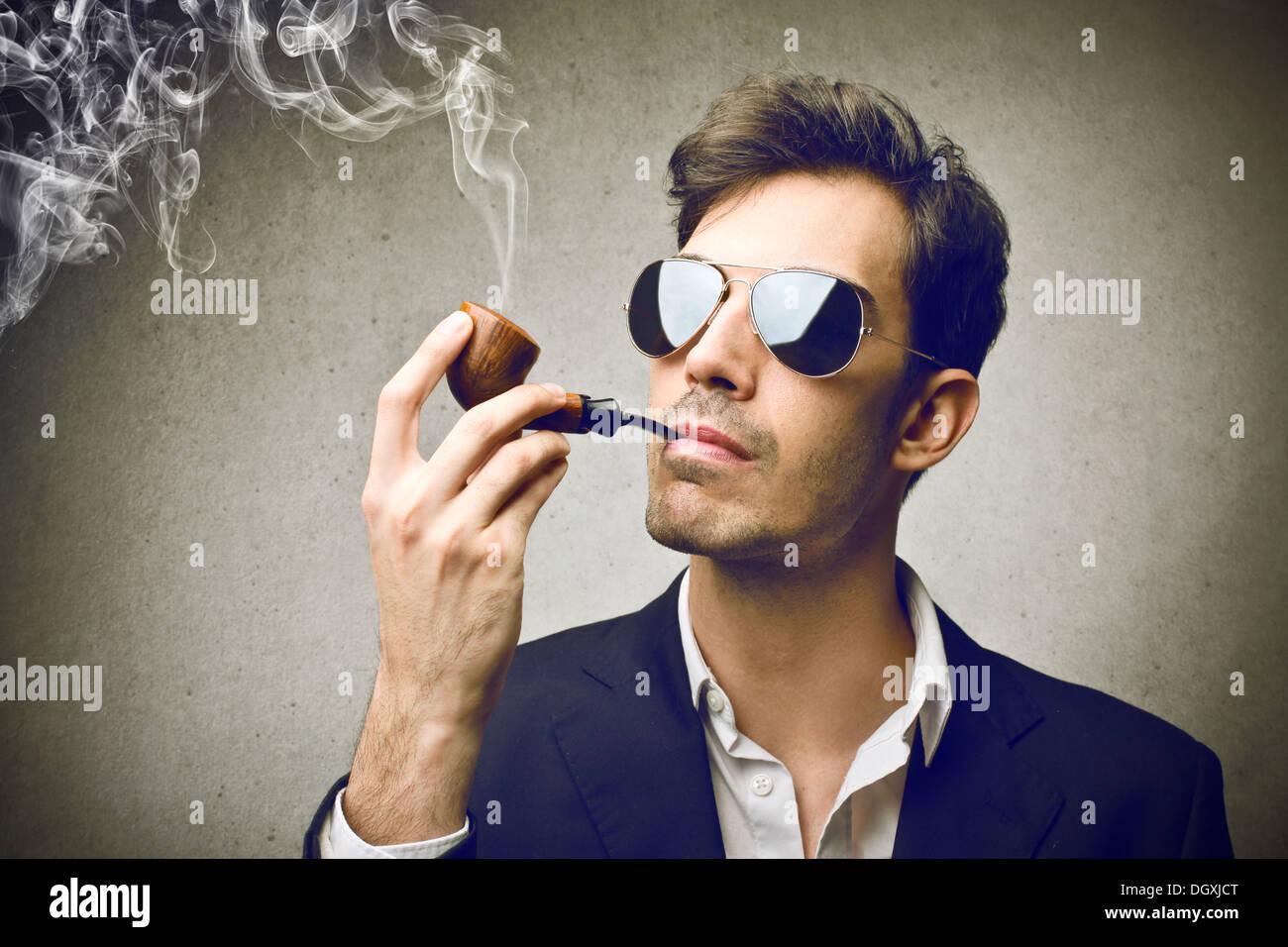 Junge und elegante Mann raucht eine Pfeife Stockbild