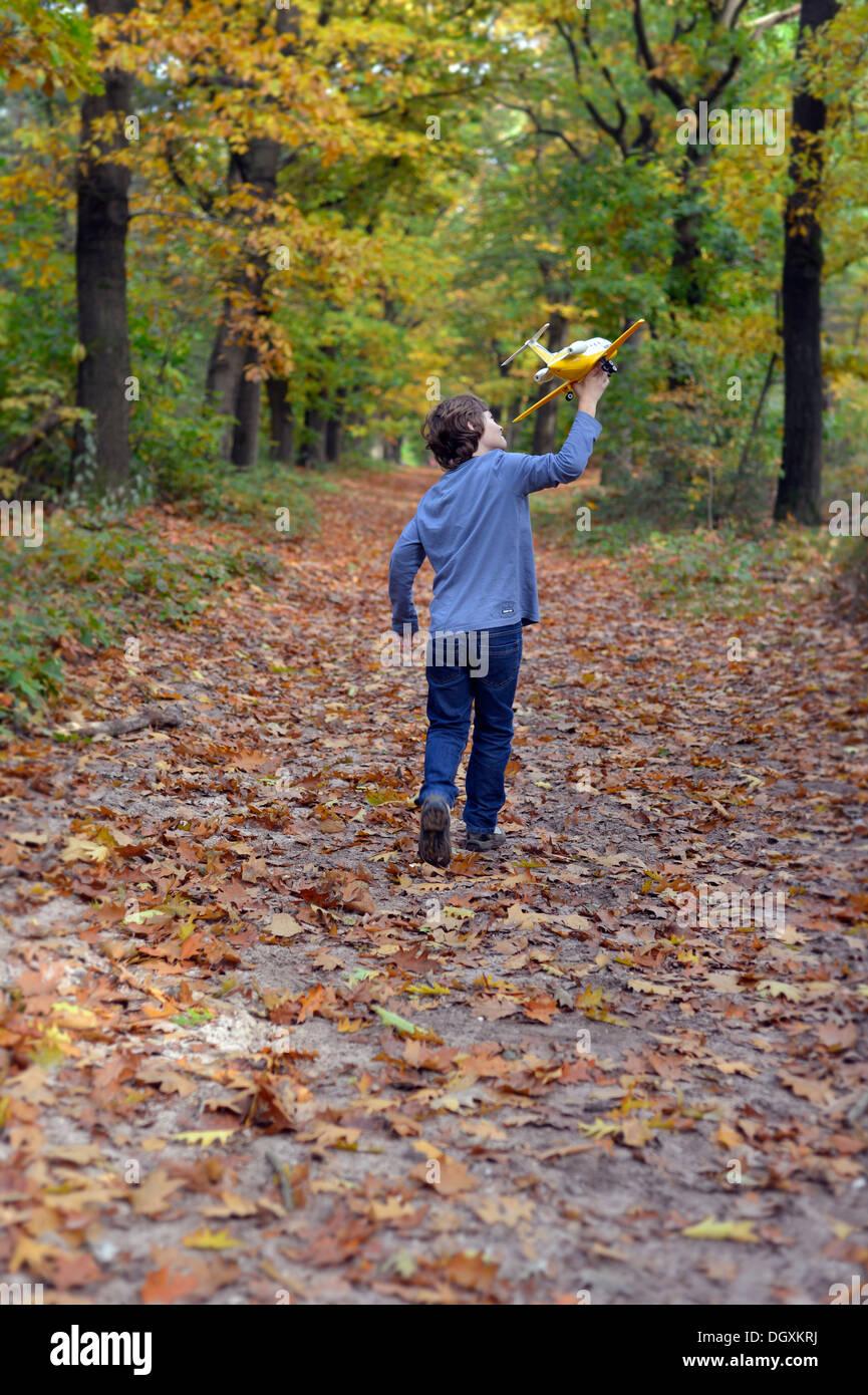 Jungen spielen mit einem Spielzeugflugzeug in einem Wald Stockbild