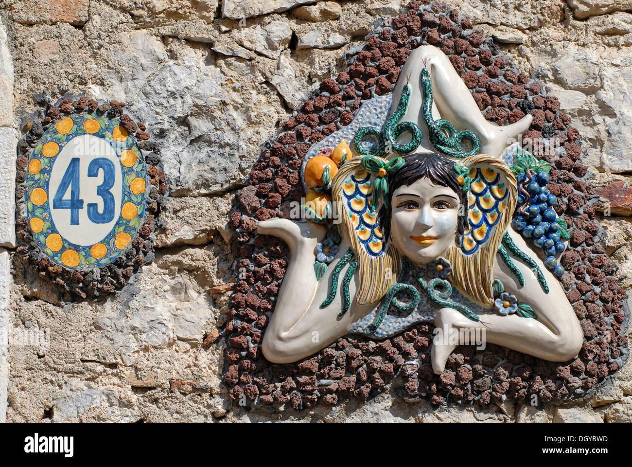 Das Symbol von Sizilien, ein Mädchenkopf umgeben von Schlangen und kleinen Flügeln mit drei laufenden angewinkelten Beinen, Sonnenrad, an einer Wand Stockbild