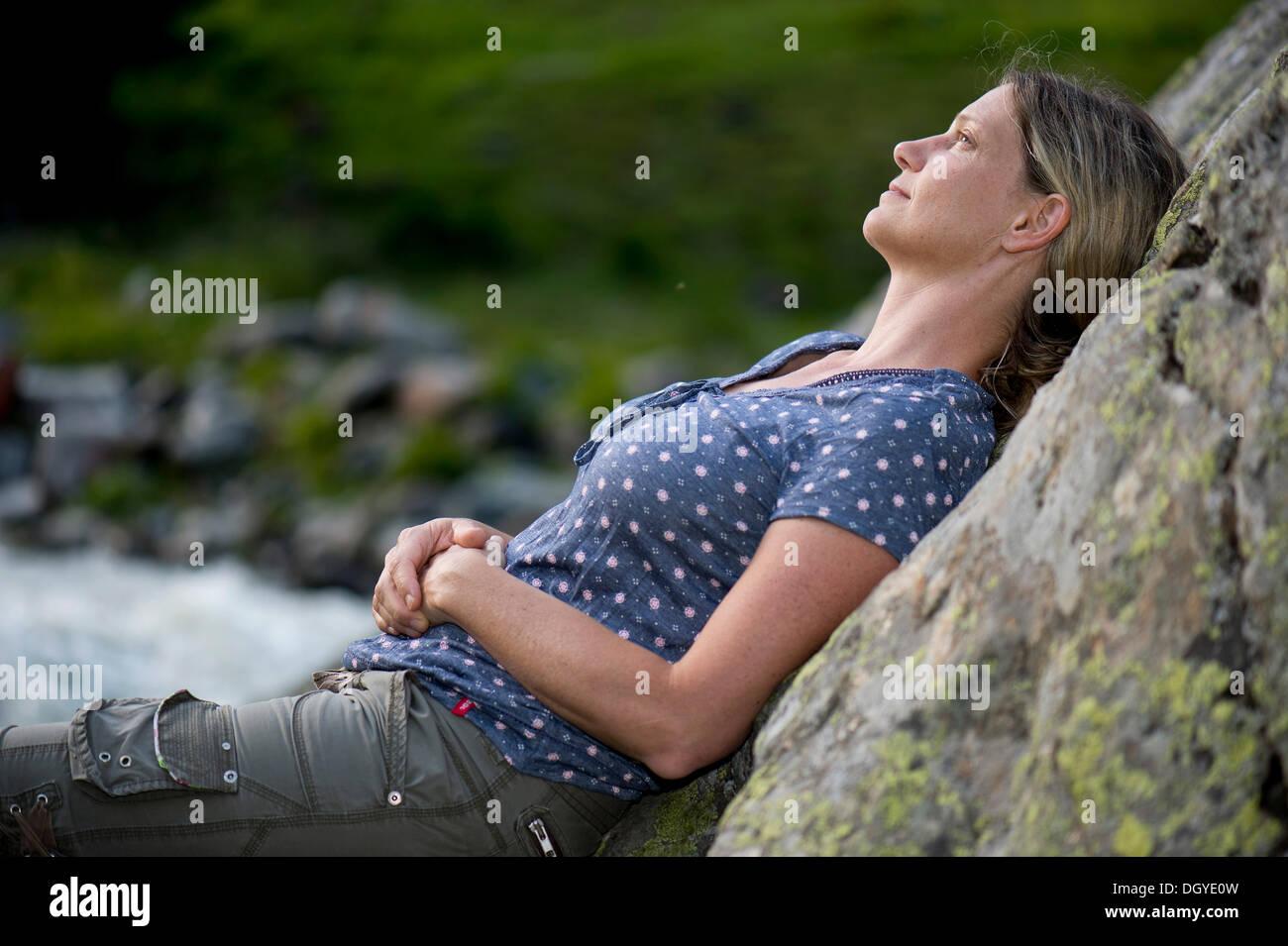 Frau, Anfang 40, verträumt an einem Felsen gelehnt Stockbild