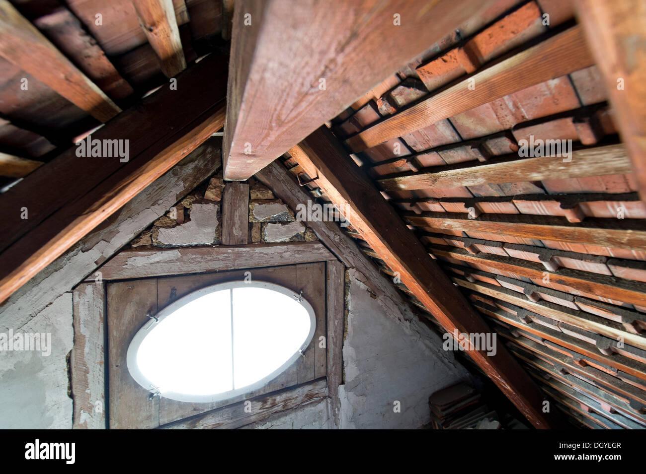 Ein ovales Fenster, Holzbalken, Dachboden, Holzdach eines alten Gebäudes, Stuttgart, Baden-Württemberg Stockfoto