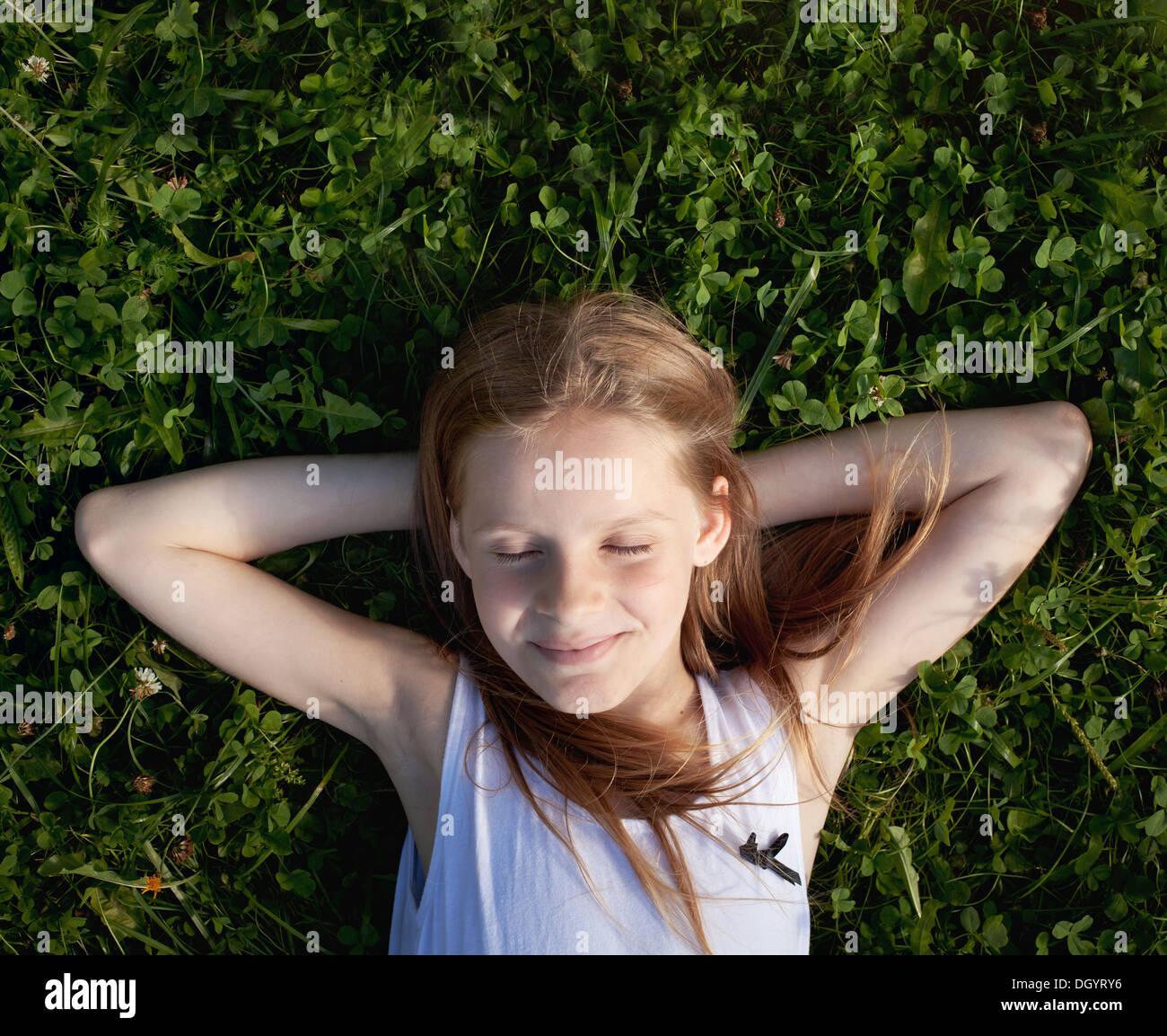 glückliche kleine Mädchen träumen auf dem Rasen und Sommer genießen Stockbild