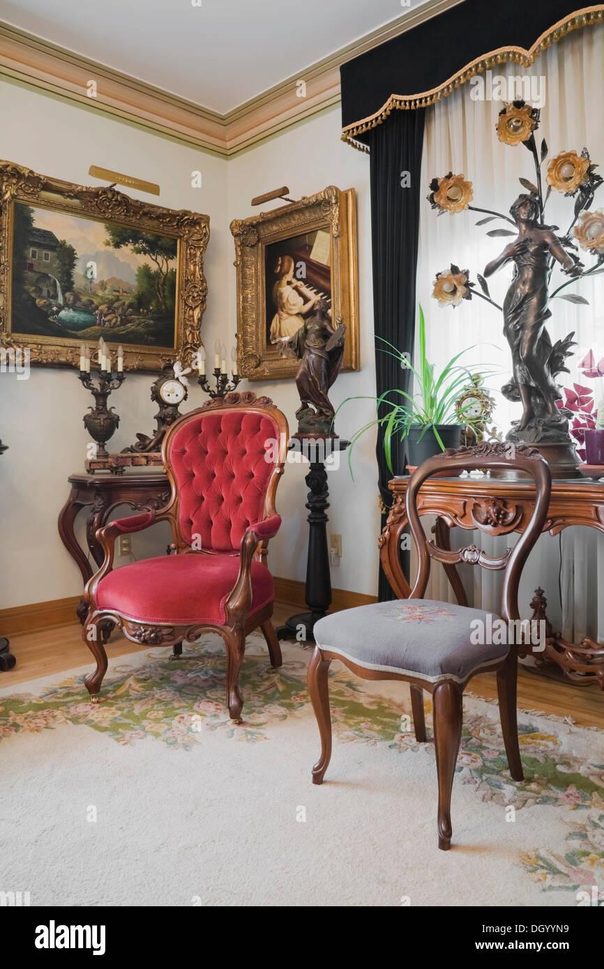Antike Stühle und Möbel schmücken ein Wohnzimmer in ein ...