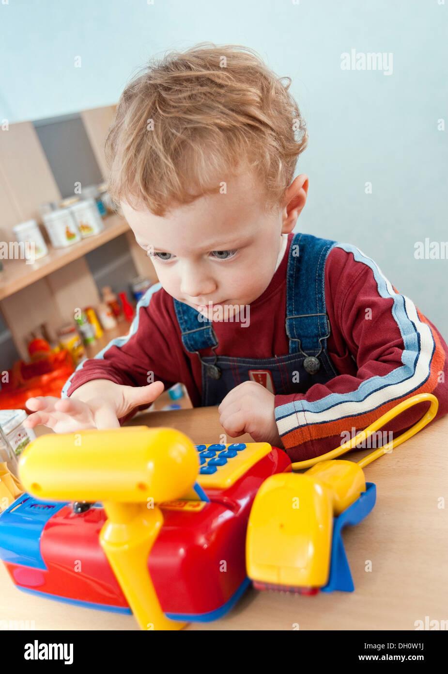 Junge, 2, das Spiel mit der Registrierkasse ein Spielzeug-Lebensmittelgeschäft Stockbild