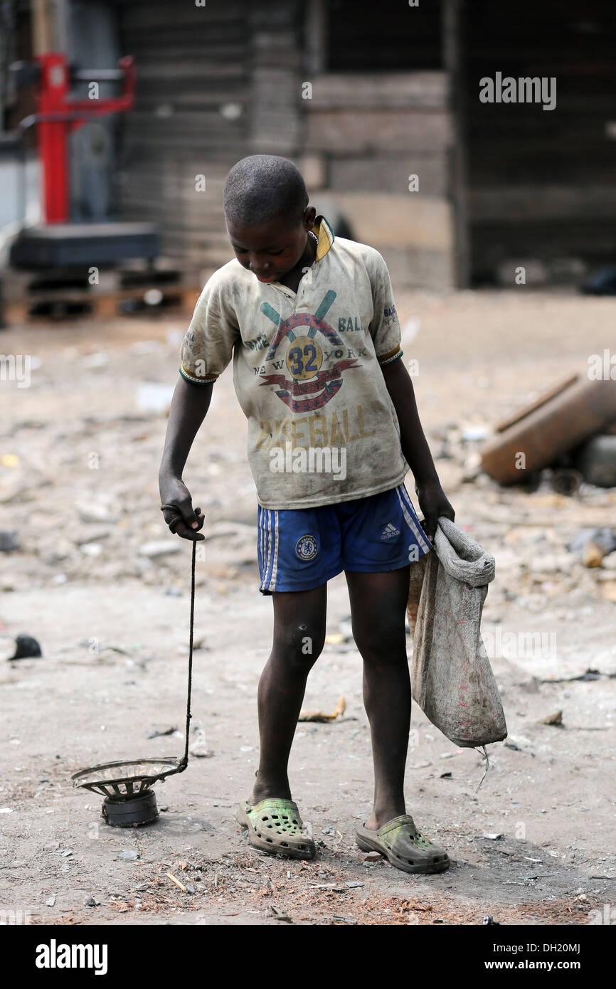 Junge sammelt Eisenteile mit einem Magneten auf der elektronischen Müllhalde Agbogbloshie, Accra, Ghana Stockbild