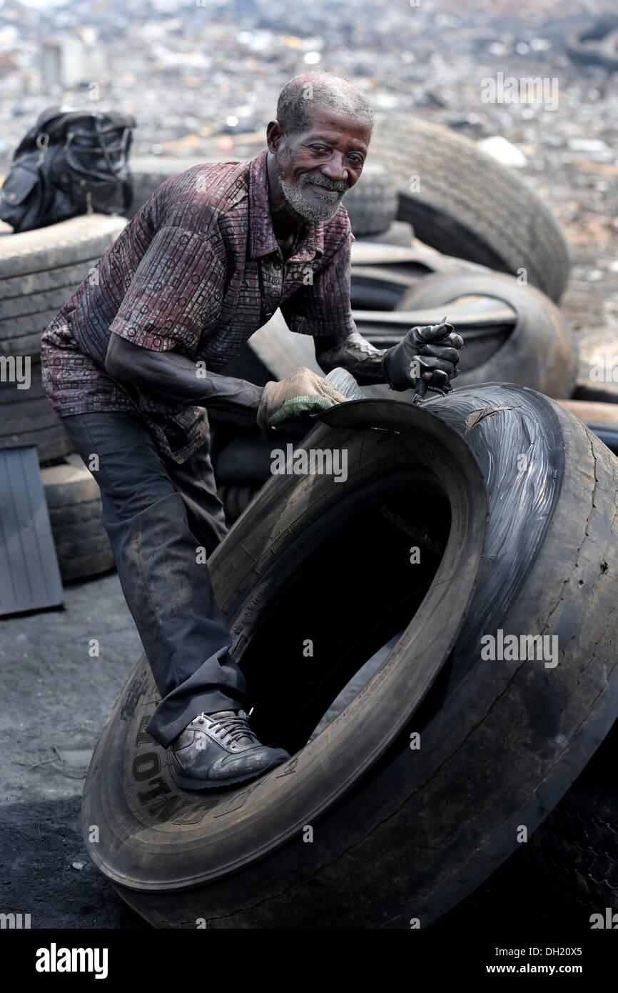Alter Mann macht Gummischuhe aus Reifen, Deponie Agbogbloshie, Accra, Ghana Stockbild